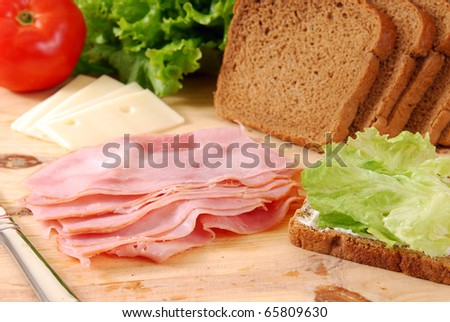Thin sliced deli ham being made into a sandwich - stock photo