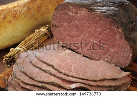 Thin sliced roast beef and a loaf of brad - stock photo