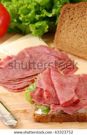 Thin sliced roast beef on a slice of bread - stock photo