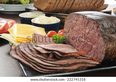 Thin sliced roast beef with cheese, bread and other sandwich fixings - stock photo
