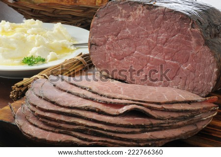 Thin sliced roast been with mashed potatoes on a dinner table - stock photo