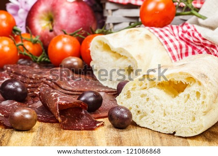 Thin slices of dry , smoked prosciutto with bread and tomatoes, Selective focus - stock photo