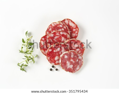 thin slices of french dry salami, thyme and peppercorns on white background - stock photo