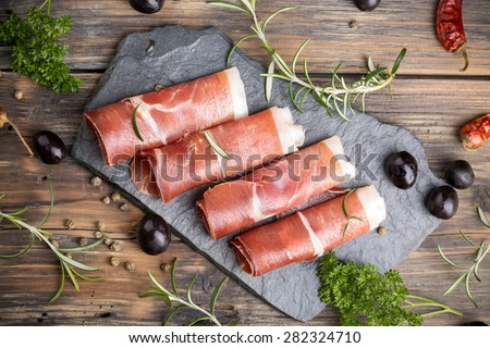 Thin slices of prosciutto with olives and herbs - stock photo