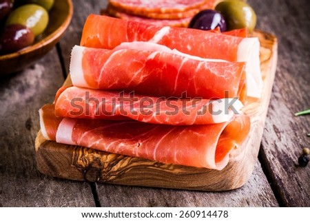 thin slices of prosciutto with olives on wooden cutting board - stock photo