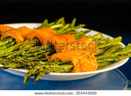 Thin slices of smoked salmon wrapped around sauteed asparagus.  Selective focus with shallow depth of field. - stock photo