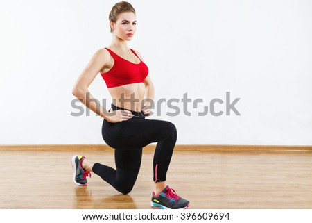 Thin sportive girl wearing snickers, black leggings and red short top doing squatting at gym holding hands on waist, fitness, white wall and wooden floor at background. - stock photo