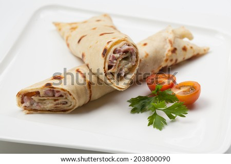 Thin twisted pancakes stuffed with ham and sauce