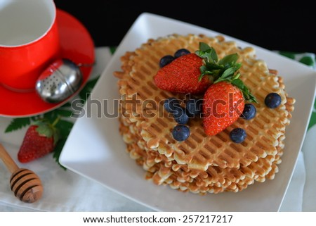 Thin waffles with berries on a black background