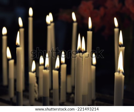 Thin white candles in catholic church - stock photo