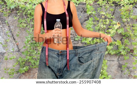 Thin woman stuck in huge pants with a water bottle and a measuring tape - stock photo