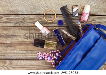 Things from open lady handbag. women's purse on wood background. Cosmetics and women's accessories fell out of the blue handbag. Toned image.  - stock photo