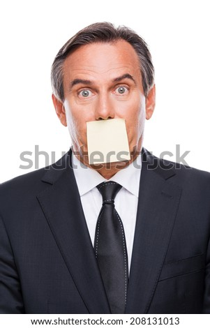 Things to do. Portrait of frustrated mature man in formalwear and adhesive note on his mouth standing against white background and looking at camera