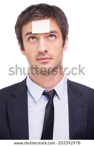 Things to do. Portrait of frustrated young man in formalwear and adhesive note on his forehead standing against white background  - stock photo