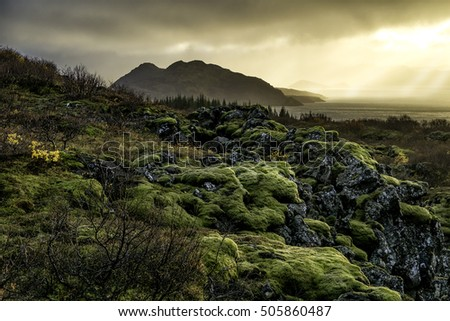 Thingvellir national park, Iceland, shot in autumn with the sunlight breaking out of low rainclouds over the lake. Moss grown lava in the foreground.