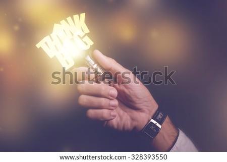 Think big business ideas visual metaphor, businessman with light bulb, retro toned image, selective focus. - stock photo