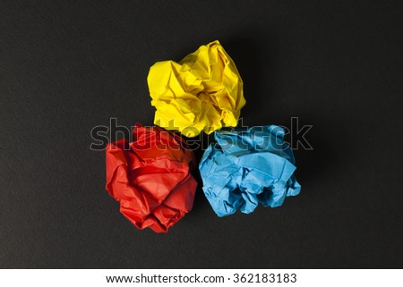 Think different. Crumpled color papers on black background