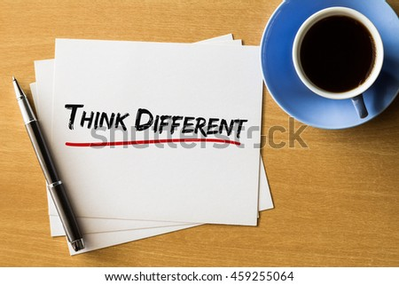 Think different - handwriting on papers with cup of coffee and pen, concept - stock photo