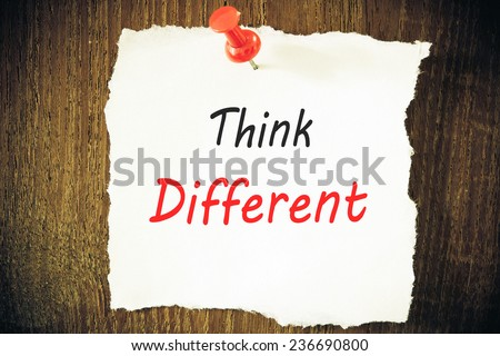 Think different written on piece of paper, on a wood background. - stock photo