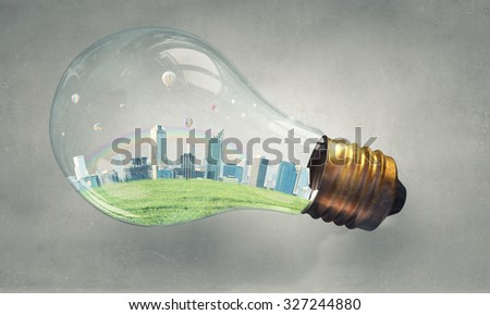 Think green concept with modern cityscape inside of light bulb