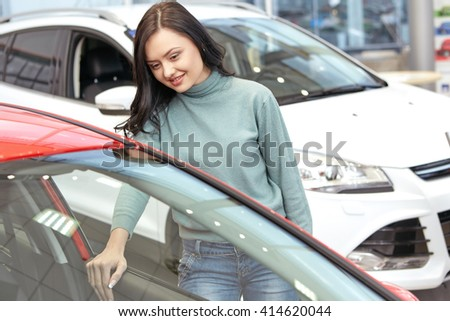 Think I found one. Young cheerful woman buying a new car examining interior of the car at the car salon - stock photo