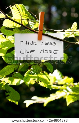 Think less live more inspirational message written on a white card hanging on a green leafy branch by a wooden clothes peg. - stock photo