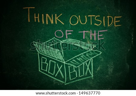 Think outside of the box, handwritten message on a chalkboard - stock photo