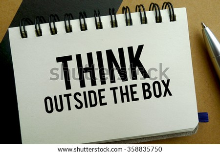 Think outside the box memo written on a notebook with pen