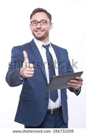 Think positively. Upbeat bearded businessman holding  laptop and pointing the thumb up expressing positivity