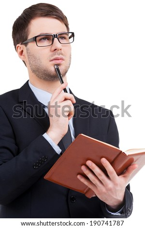 Thinking about business solutions. Confident young man in formalwear holding note pad and looking away while standing isolated on white