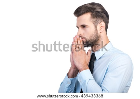 Thinking about future. Side view of thoughtful young handsome man in shirt and tie holding hand on chin and looking away while standing against white background