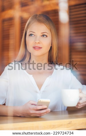 Thinking about him. Through a glass shot of beautiful young woman holding mobile phone and looking away while enjoying coffee in cafe  - stock photo