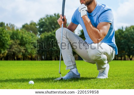 Thinking about next shot. Cropped image of young golfer kneeling near the golf ball and holding hand on chin  - stock photo