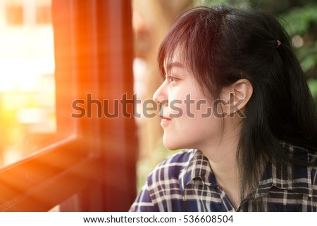 thinking about or missing passed good memory . asian women have a vision look out far away to bright window with sunshine