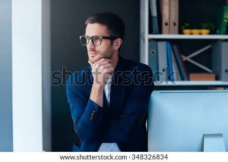 Thinking about solution. Confident young man in smart casual wear holding hand on chin and looking at camera while leaning at computer monitor in office - stock photo