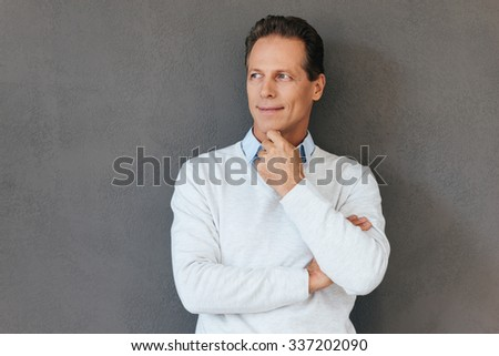 Thinking about solution. Thoughtful mature man holding hand on chin and looking away while standing against grey background  - stock photo
