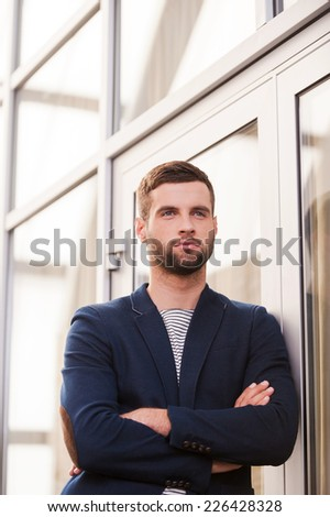 Thinking about solutions. Low angle view of confident young man in smart casual wear keeping arms crossed and looking away while standing indoors  - stock photo