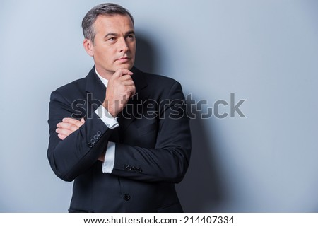 Thinking about solutions. Thoughtful mature man in formalwear holding hand on chin and looking away while standing against grey background - stock photo