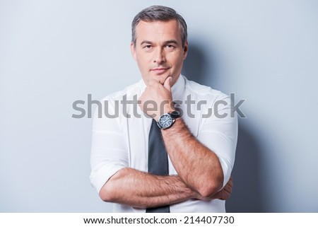 Thinking about your problems. Thoughtful mature man in shirt and tie holding hand on chin and looking at camera while standing against grey background - stock photo