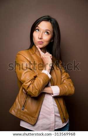 Thinking Asian business woman smiling looking to the side. Beautiful young mixed race Asian Caucasian woman professional isolated on brown background. - stock photo