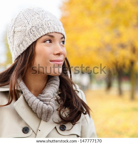 Thinking autumn woman looking at fall forest smiling happy walking in colorful autumn foliage outdoors. Happy female model looking thoughtful at copy space outside in beautiful nature. Girl in 20s. - stock photo