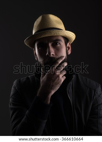 Thinking bearded man wearing straw hat touching beard looking at camera. Low key dark shadow portrait over black background. - stock photo