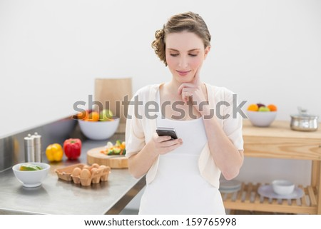 Thinking beautiful woman using her smartphone standing in the kitchen at home - stock photo