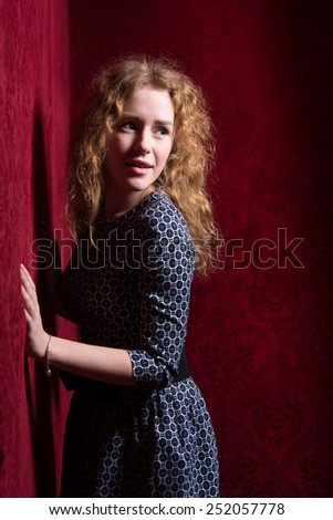 Thinking beautiful young woman looking to the side at red copyspace. Funky fresh and playful Caucasian smiling happy and joyful on red background. - stock photo