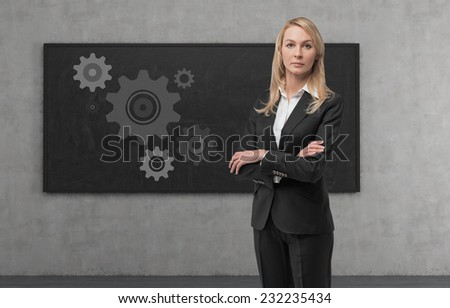 Thinking blonde business woman with gears - A concept of well organized work process.  - stock photo