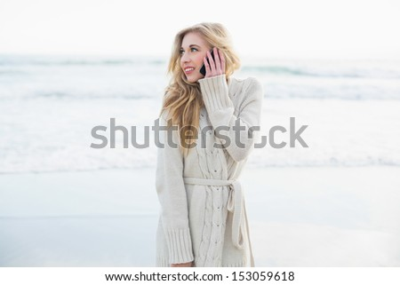 Thinking blonde woman in wool cardigan making a phone call on the beach - stock photo