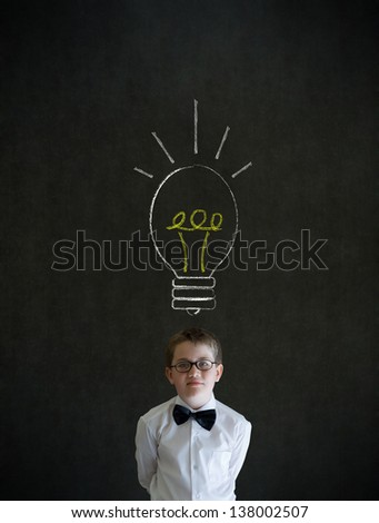 Thinking boy dressed up as business man with bright idea chalk background lightbulb on blackboard background