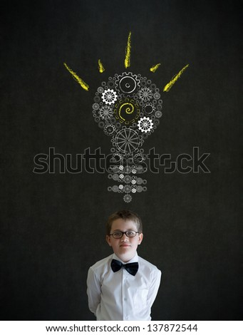 Thinking boy dressed up as business man with bright idea gear cog lightbulb on blackboard background - stock photo