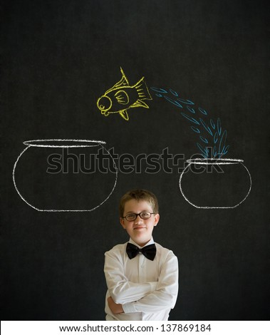 Thinking boy dressed up as business man with chalk fish jumping from small bowl to big bowl on blackboard background - stock photo