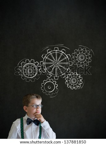 Thinking boy dressed up as business man with chalk turning gear cogs or gears on blackboard background - stock photo